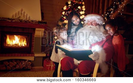 Santa Claus reading magic book with little children