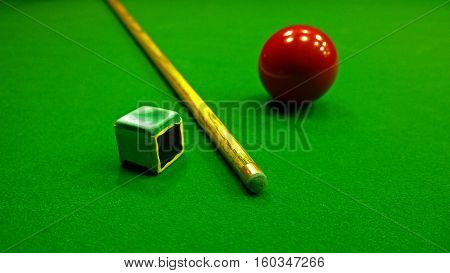Cue, chalk and snooker ball are on the table