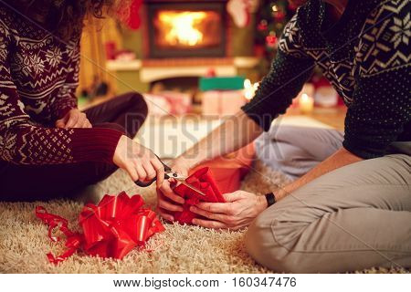 Close up of couple's hands packing Christmas gifts, concept