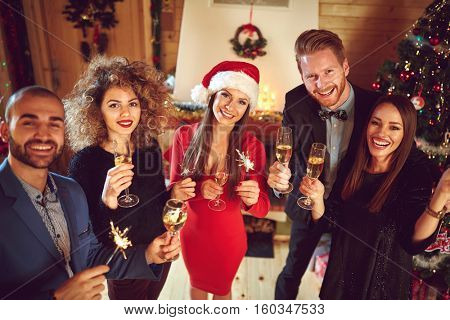 Young people celebrating New Year with sparkles and Champaign