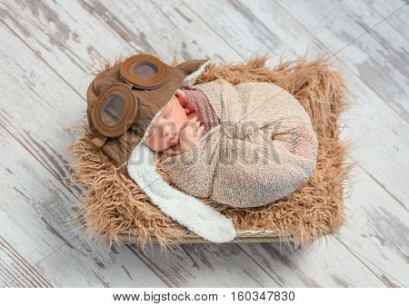 funny sleeping wrapped newborn baby with pilot hat on fluffy blanket in basket, top view