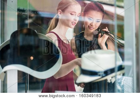 Two pretty young women window shopping pointing through the glass at a display of hats inside the fashion store , reflections on the glass