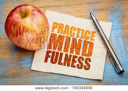 Practice mindfulness - motto or resolution on a napkin with an apple