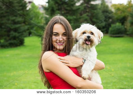 Girl with puppy. Portrait of attractive happy smiling young woman holding cute little dog, summer park outdoor.