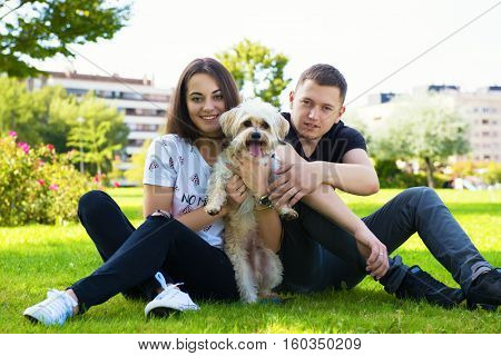 Young couple with puppy. Portrait of attractive happy smiling young woman and man holding cute little dog, summer park outdoor.