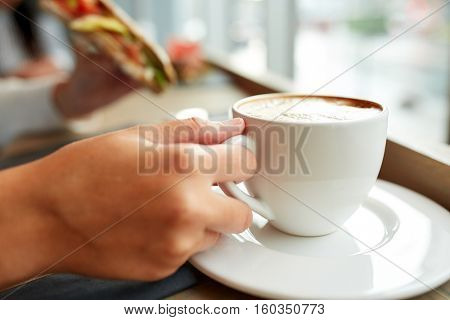 food, dinner and people concept - woman drinking coffee and eating panini sandwich for breakfast or lunch at cafe