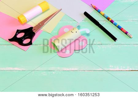 Funny paper butterfly crafts, scissors, marker, glue stick, pencil, colored paper, pencil on green wooden background with blank place for text. Kids summer diy in kindergarten or at home
