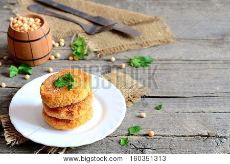 Fried pea cutlets on a plate. Healthy vegan cutlets cooked from yellow dried peas and decorated with parsley. Fork, knife on an old wooden background with copy space for text. Vegan food idea. Closeup
