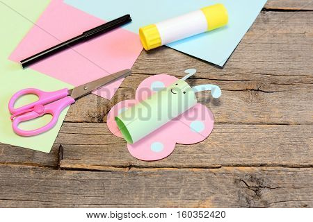 Cute paper butterfly crafts, scissors, marker, glue stick, colored paper set, pencil on old wooden table. Kids working place. Summer preschooler art craft and activity concept. Closeup