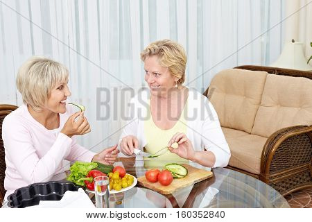 Two smiling women sitting at the table and preparing salad together