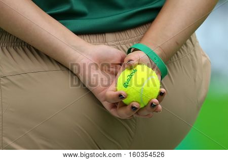 RIO DE JANEIRO, BRAZIL - AUGUST 11, 2016: Ball girl holding Wilson tennis ball during  match of the Rio 2016 Olympic Games at the Olympic Tennis Centre