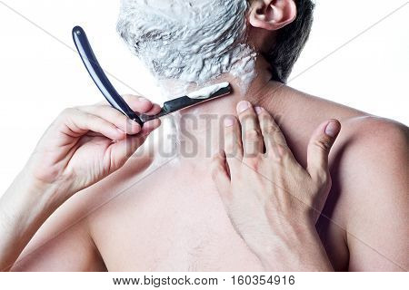 Young man with old-fashioned straight razor shaves his beard in the bathroom. Closeup of mature man shaving his face passing the razor for the beard isolated over white background