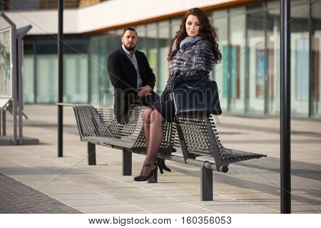 Happy young couple on city street. Man and woman sitting on bench. Stylish fashion model outdoor