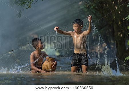 Childrens  playing in the creek water happily,Children fishing in the river,The boys are enjoying playing the stream.