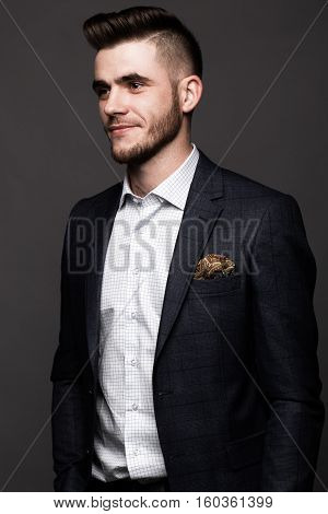 A solid man with a beard and mustache in a classic fashionable suit. Photos shot in the studio.
