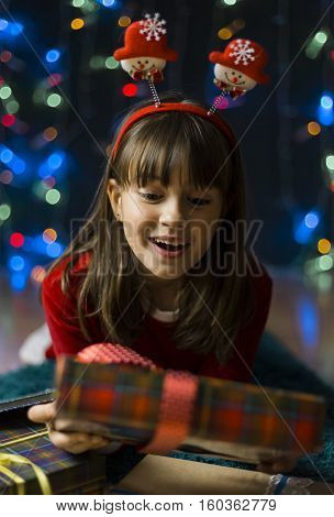 Young smiling girl wearing red dress surprized by gift box