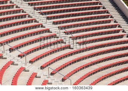 empty plastic red seats on football stadium or amphitheater