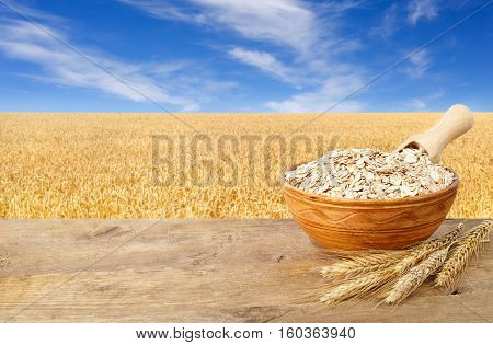 Oat flakes in bowl. Ears of oats and oatmeal in bowl on wooden table with field on the background. Golden field and blue sky. Uncooked porridge