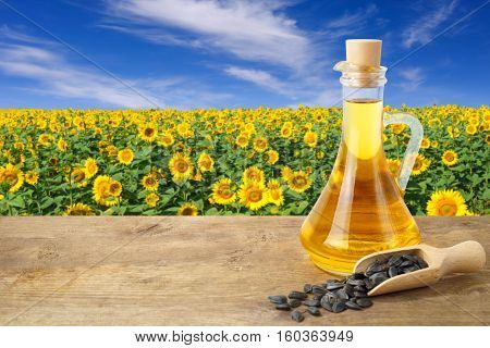 Sunflower oil in glass bottle and seeds on wooden table with sunflower field on the background. Sunflower field with blue sky. Photo with copy space area for a text