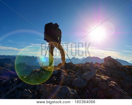 Lens Flare Defect.  Silhouette Of Man With Hood,backpack And Poles In Hand. Man Walk