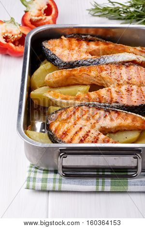 Grilled salmon steak with potatoes on oven tray