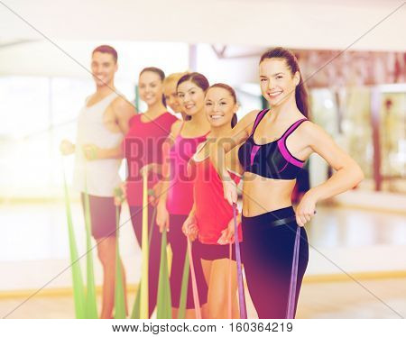 fitness, sport, training, gym and lifestyle concept - group of smiling people working out with rubber bands in the gym