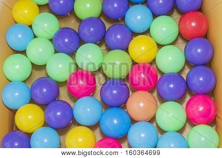 A colorful inflatable balls floating in a bathtub children .