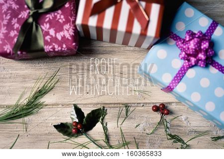 the text frohe weihnachten, merry christmas in german and some gifts wrapped in different papers and tied with ribbons of different colors, and some natural ornaments, on a rustic wooden surface