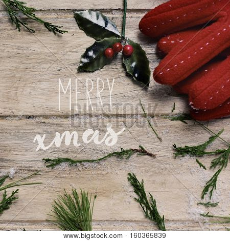 high-angle shot of a twig of holly, a pair of cozy red gloves and some natural twigs on a rustic wooden surface and the text merry xmas in the center