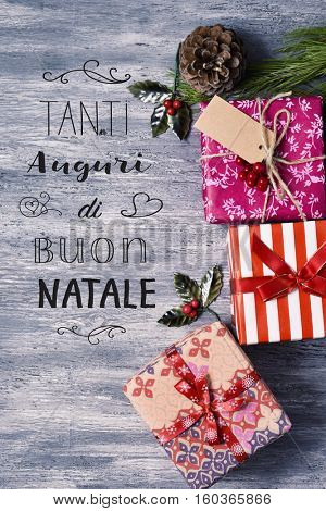 high-angle shot of some cozy christmas gifts on a rustic wooden surface and the text text tanti auguri di buon natale, merry christmas written in italian