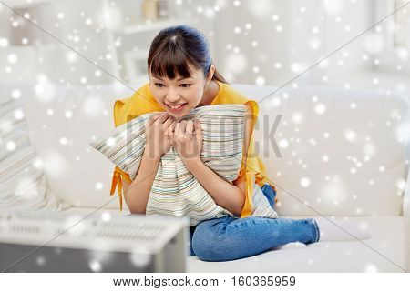 television, entertainment, leisure and people concept - happy asian young woman watching tv at home over snow