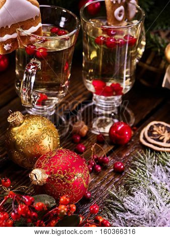 Two glasses of hot tea with wine, close-up. Lovely composition with Christmas balls on wooden table.