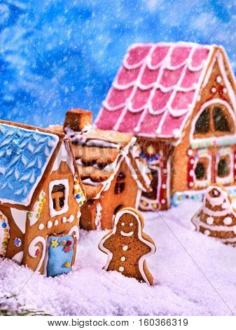 Street consisting of gingerbread houses with glaze. Gingerbread man walks on a snow-covered street. Gingerbread Christmas Tree and snowfall.