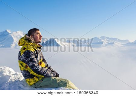 Alpine winter mountain landscape with man sitting above low clouds. French Alps covered with snow in sunny day. Val-d'Isere, France
