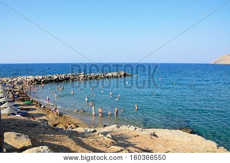 PANORMOS, CRETE - SEPTEMBER 15, 2016 - Tourists relaxing on the sandy beach with views towards the breakwater and sea Panormos Crete Greece Europe, September 15, 2016.