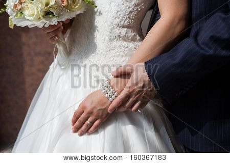 Bride and groom holding hands. The groom in a dark suit the bride in a gown of white lace.