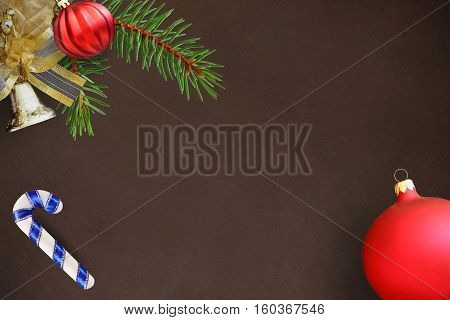 Christmas fir branch red wavy dull ball stick and bell on a dark background