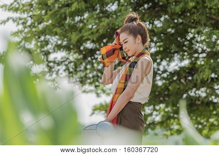 Woman watering plants in garden with sunny.