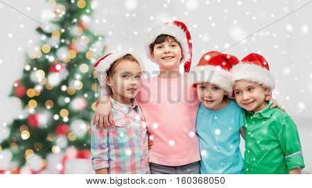 childhood, winter holidays, friendship and people concept - group of happy smiling little children in santa hats hugging over christmas tree and snow