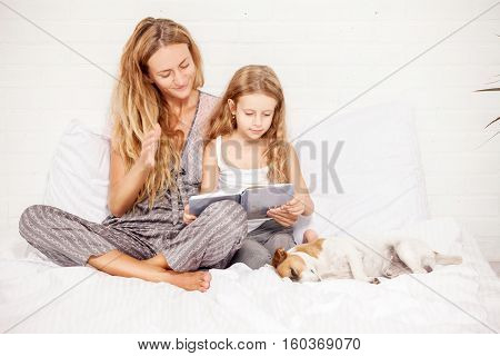 Woman with child reading book. Happy family at home. Mother with daughter in bed