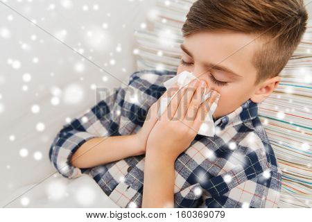healthcare, rhinitis, people and medicine concept - close up of ill boy with flu lying in bed and blowing his nose at home over snow