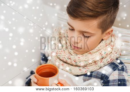 childhood, healthcare, people and medicine concept - close up of ill boy with flu lying in bed and drinking tea at home over snow