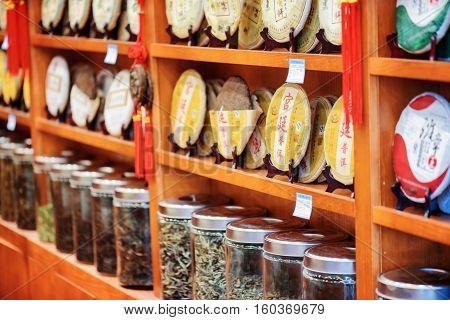 Disks Of Yunnan Puer And Tea In Glass Jars At Tea Shop, Lijiang