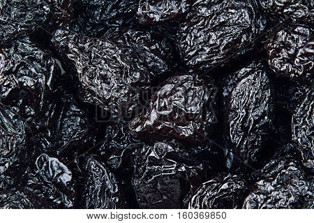 Prune close up background. Heap of glossy black prunes. Top view.