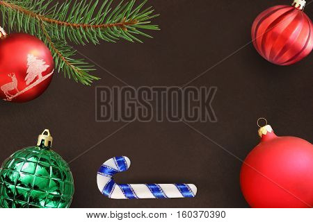 Dark background with Christmas fir branch stick red wavy dull and green ribbed ball. Top view.