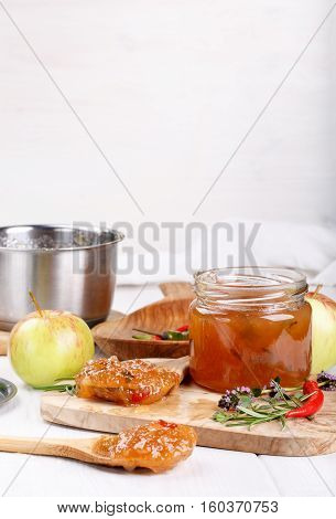 Chilli pepper apple jam with herbs. Copy space.