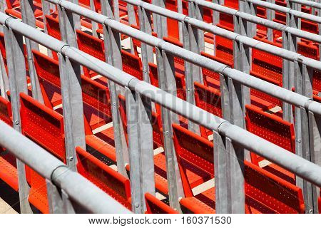 Row of empty red seats in a sports stadium with metal railings viewed diagonally close up in a full frame view