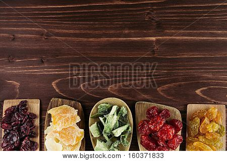 Assortment of dried fruits in spoons on brown wooden background. Decorative border of dry exotic fruit. Top view.