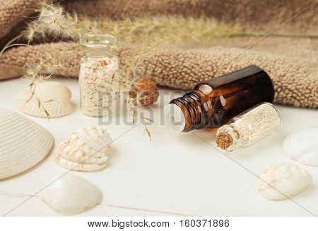 Light beige spa treatment setting. Essential oil, bathroom terry towel, seashells, sand decor. Beach themed summer skincare.