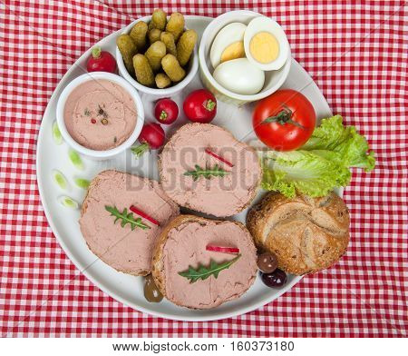 plate with slices of bread with home made pate vegetables and eggs